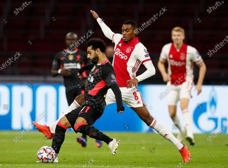 Stock Picture of Liverpool's Mohamed Salah, left, controls the ball in front of Ajax's Ryan Gravenberch, during the group D Champions League soccer match between Ajax and Liverpool at the Johan Cruyff ArenA in Amsterdam, Netherlands
