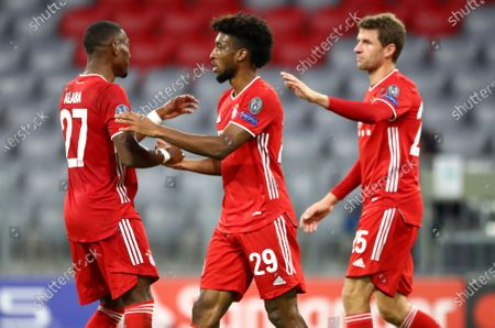 Bayern Munich's Kingsley Coman, centre, is congratulated by teammate David Alaba, left, after scoring his team's first goal during the Champions League Group A soccer match between Bayern Munich and Atletico Madrid at the Allianz Arena in Munich, Germany