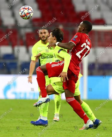 Bayern Munich's David Alaba, right, and Atletico Madrid's Joao Felix battle for the ball during the Champions League Group A soccer match between Bayern Munich and Atletico Madrid at the Allianz Arena in Munich, Germany