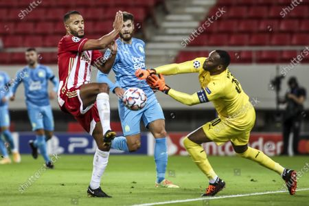 Olympiacos's Youssef El-Arabi (L) vies for the ball with Marseille's goalkeeper Steve Mandanda during the UEFA Champions League  soccer match between Olympiacos Piraeus and Olympique Marseille held at Georgios Karaiskakis Stadium in Piraeus, Greece, 21 October 2020.