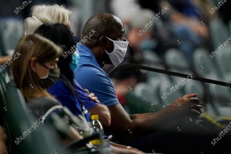 Magic Johnson watches during the fourth inning in Game 2 of the baseball World Series between the Los Angeles Dodgers and the Tampa Bay Rays, in Arlington, Texas