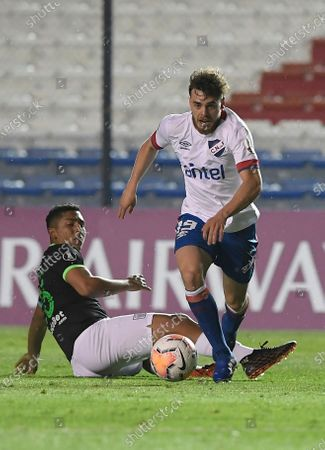 Alfonso Trezza of Uruguay's Nacional, right, takes control of the ball after challenged by Alberto Rodriguez of Peru's Alianza Lima during their Copa Libertadores soccer match in Montevideo, Uruguay