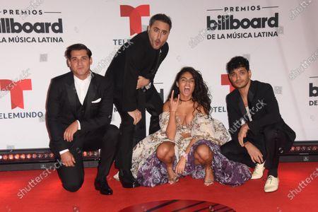 Jessie Reyez poses with Jesús Navarro, Julio Ramírez Eguía, and Bibi Marín of Reik on the red carpet at the Billboard Latin Music Awards