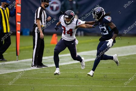 Houston Texans cornerback John Reid (34) battles with Tennessee Titans cornerback Tye Smith (23) on a punt play during the first half of an NFL football game, in Nashville, Tenn