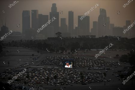 Los Angeles Dodgers' fans watch game two of the World Series 2020 between the Tampa Bay Rays and Los Angeles Dodgers, at a drive-in is organized on the grounds of Dodger Stadium (foreground) amid the coronavirus pandemic in Los Angeles, California, USA, 21 October 2020.