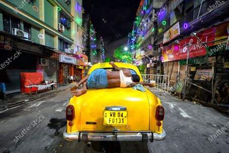 A Taxi driver seen sleeping on his Taxi in the middle of a decorated street during the Durga Puja Festival.