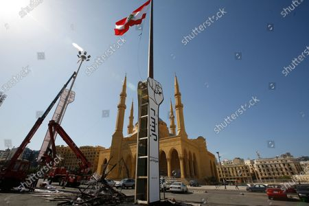 Workers install two fists as symbol of the October revolution, in front of the Al-Amin Mosque, in the place of the fist that was burned by the supporters of Saad Hariri yesterday evening, in downtown Beirut, Lebanon, 22 October 2020. President Michel Aoun is holding parliamentary consultations on 22 October 2020 to choose and appoint a new prime minister, and according to the media in Beirut, the parliamentary blocs are heading to name  Saad Hariri, but the blocs affiliated with Hezbollah, the Lebanese Forces and the Free Patriotic Movement did not choose anyone.
