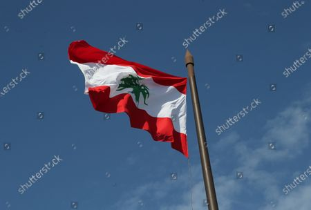 Stock Image of A giant Lebanese flag flutters at the place of two fists as symbol of the October revolution, in front of the Al-Amin Mosque, in the place of the fist that was burned by the supporters of Saad Hariri yesterday evening, in downtown Beirut, Lebanon, 22 October 2020. President Michel Aoun is holding parliamentary consultations on 22 October 2020 to choose and appoint a new prime minister, and according to the media in Beirut, the parliamentary blocs are heading to name  Saad Hariri, but the blocs affiliated with Hezbollah, the Lebanese Forces and the Free Patriotic Movement did not choose anyone.