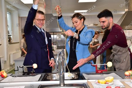 Crown Princess Victoria and Prince Daniel visit the Rinman special school in Eskilstuna, Sodermanland county. Here they help student Didar during the home economics class with the todays theme, apples.