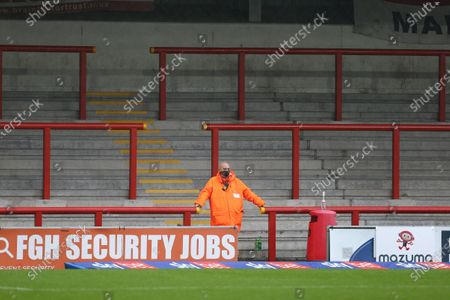 A lone steward stands guard in front of empty stands