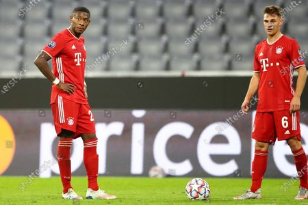 Bayern's David Alaba, left, and Joshua Kimmich wait for a free kick during the Champions League Group A soccer match between Bayern Munich and Atletico Madrid at the Allianz Arena in Munich, Germany