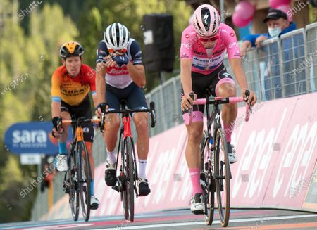 Portuguese rider Joao Almeida (R) of the Deceuninck Quick-Step team and Italian rider Vincenzo Nibali (C) of the Trek Segafredo team react while crossing the finish line of the 18th stage of the 2020 Giro d'Italia cycling race over 207km from Pinzolo to Laghi Di Cancano, Italy, 22 October 2020. Almeida lost the overall leader's pink jersey.