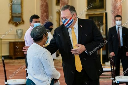 Stock Image of Secretary of State Mike Pompeo, right, congratulates a new American during a naturalization ceremony co-hosted by U.S. Citizenship and Immigration Services Deputy Director for Policy Joseph Edlow and USCIS Washington District Director Ron Rosenberg at the State Department, in Washington