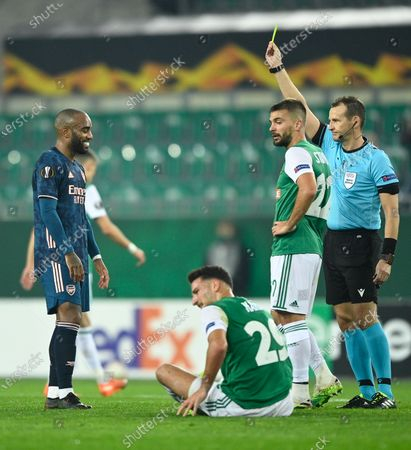 Alexandre Lacazette (L) of Arsenal is booked by Czech referee Pavel Kralovec (R) during the UEFA Europa League group B soccer match between SK Rapid Vienna and Arsenal FC in Vienna, Austria, 22 October 2020.