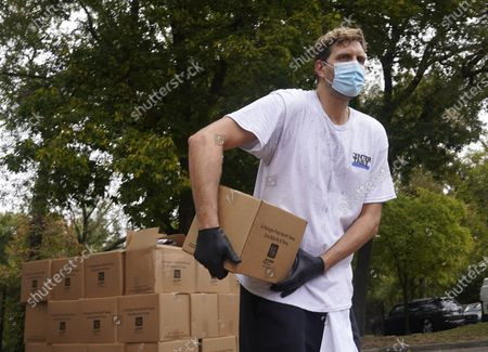Stock Image of Former NBA basketball player Dirk Nowitzki of Germany, Wearing a mask to prevent to spread of COVID-19, helps distribute food aid to the public during a North Texas Food Bank drive-thru event, in Dallas