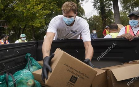 Former NBA basketball player Dirk Nowitzki of Germany, Wearing a mask to prevent to spread of COVID-19, helps distribute food aid to the public during a North Texas Food Bank drive-thru event, in Dallas