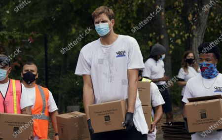 Stock Picture of Wearing a mask to prevent the spread of COVID-19, former NBA basketball player Dirk Nowitzki, of Germany, helps other volunteers distribute food aid to the public during a North Texas Food Bank drive-thru event, in Dallas