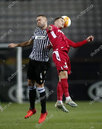 PAOK's Sverrir Ingi Ingason, left, and Omonia's Adam Lang jump for the ball during the Europa League group E soccer match between PAOK and Omonoia at Toumba stadium in the northern city of Thessaloniki, Greece