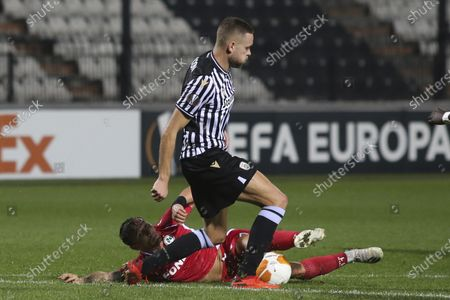 Omonia's Eric Bautheac, bottom, tries to stop PAOK's Sverrir Ingi Ingason during the Europa League group E soccer match between PAOK and Omonia at Toumba stadium in the northern city of Thessaloniki, Greece