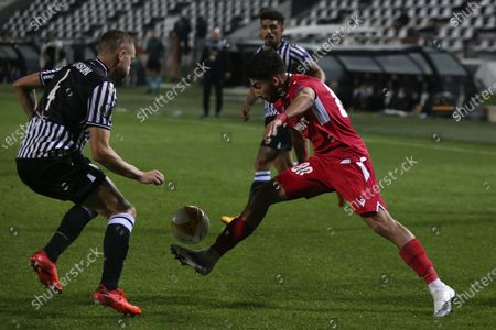 Omonia's Andronikos Kakoullis, right, controls the ball as PAOK's Sverrir Ingi Ingason defends during the Europa League group E soccer match between PAOK and Omonia at Toumba stadium in the northern city of Thessaloniki, Greece
