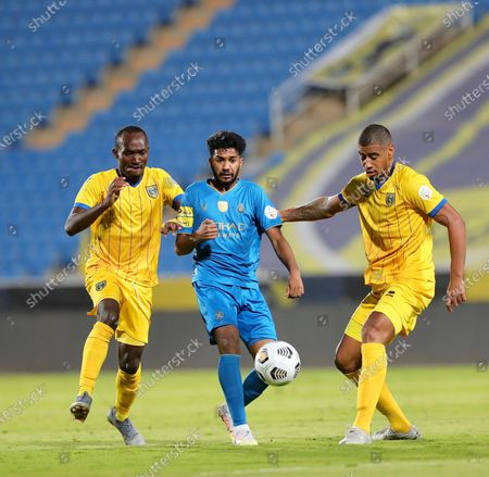 Al-Nassr's player Khalid Al-Ghannam (C) in action against Al-Taawoun's Iago Santos (R) and Cedric Amissi (L) during the Saudi Professional League soccer match between Al-Taawoun and Al-Nassr at King Abdullah Sports City Stadium, in Buraidah, Saudi Arabia, 22 October 2020.