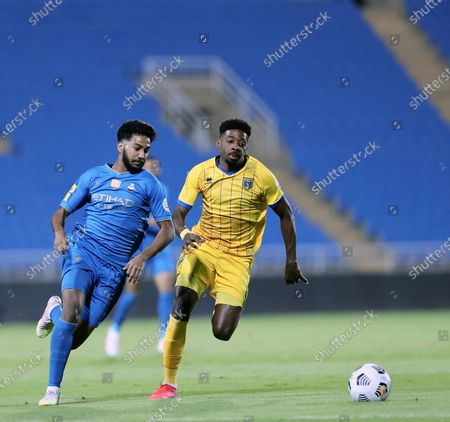 Al-Nassr's player Khalid Al-Ghannam (L) in action against Al-Taawoun's Yaseen Barnawi (R) during the Saudi Professional League soccer match between Al-Taawoun and Al-Nassr at King Abdullah Sports City Stadium, in Buraidah, Saudi Arabia, 22 October 2020.