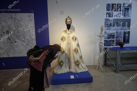 Stock Image of A visitor looks at papal ceremonial dress, a creation by Nana Cecchi Costumes, during the exhibition 'Romaison' at the Ara Pacis Museum in Rome, Italy, 22 October 2020. The exposition brings together the most important Rome's tailors of costume. 'Romaison, invented name, combines two words (Rome and maison) that tell a unique city where fashion and cinema have always generated a creative system appreciated all over the world', said mayor of the Italian capital, Virginia Raggi, during the presentation of the event.