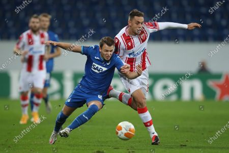 Dennis Geiger (L) of TSG 1899 Hoffenheim is tackled by Milan Rodic of Crvena Zvezda during the UEFA Europa League Group L soccer match between TSG Hoffenheim and Crvena Zvezda at PreZero-Arena in Sinsheim, Germany, 22 October 2020.