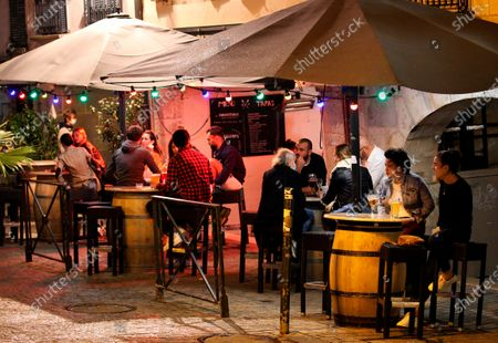 People drink in a bar terrace before the start of a new coronavirus curfew, in Bayonne, southwestern France, . Curfews loom for Italy's three largest cities face new curfews, and similar overnight off-the street rules were decided on Thursday for elsewhere in Europe, including Athens and much of France