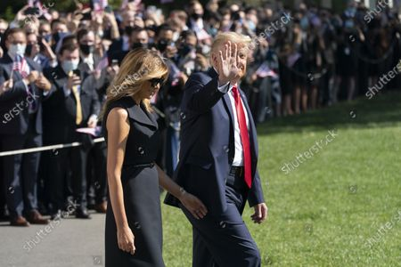 United States President Donald J. Trump waves in the direction of the media as he and first lady Melania Trump depart the White House in Washington, DC, en route to Nashville, Tennessee where the President will participate in a debate with the Democratic presidential candidate, former US Vice President Joe Biden.