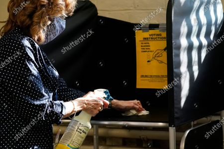 Election clerk Cheryl Lupi sanitizes a voting booth inside Haverhill City Hall during early in-person voting, in Haverhill, Mass