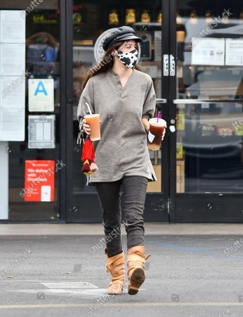 Stock Image of Scout LaRue Willis is seen on a coffee run wearing boots and a cow print mask