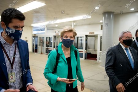United States Senator Elizabeth Warren (Democrat of Massachusetts), left, is joined by United States Senator Bob Menendez (Democrat of New Jersey), right, and other Senators as they make their way through the Senate subway for a vote at the US Capitol in Washington, DC,.