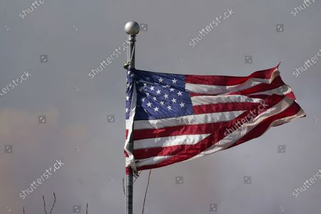 The American flag is blown by heavy winds as smoke rises from mountain ridges as a wildfire burns, near Granby, Colo