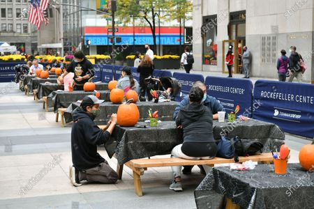 Guests participate in Maniac Pumpkin Carvers to help New Yorkers create exquisite Jack-O-Lanterns at socially distant carving class at Rockefeller Center.