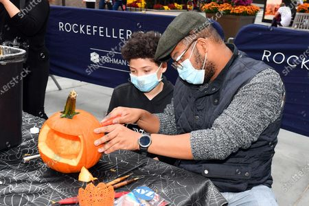 Stock obrázek na téma Guests participate in Maniac Pumpkin Carvers to help New Yorkers create exquisite Jack-O-Lanterns at socially distant carving class at Rockefeller Center.