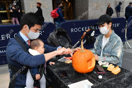 Stock fotografie na téma Guests participate in Maniac Pumpkin Carvers to help New Yorkers create exquisite Jack-O-Lanterns at socially distant carving class at Rockefeller Center.