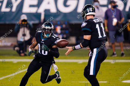 Philadelphia Eagles' Carson Wentz, right, tosses to DeSean Jackson during the first half of an NFL football game against the New York Giants, in Philadelphia