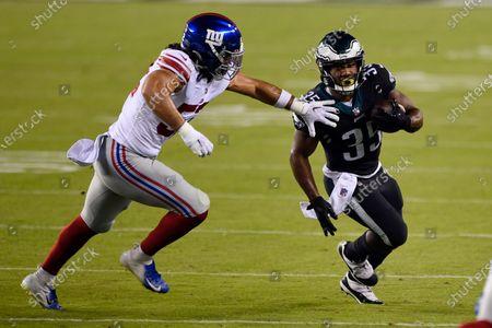 Philadelphia Eagles' Boston Scott, right, tries to slip past New York Giants' Devante Downs during the first half of an NFL football game, in Philadelphia
