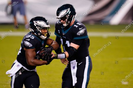 Philadelphia Eagles' Carson Wentz, right, hands off to Boston Scott during the first half of an NFL football game against the New York Giants, in Philadelphia