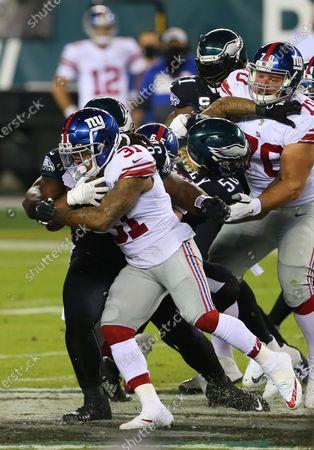 Stock Image of New York Giants' Devonta Freeman (31) is grabbed by Philadelphia Eagles' Derek Barnett (96) during an NFL football game, in Philadelphia. The Eagles defeated the Giants 22-21