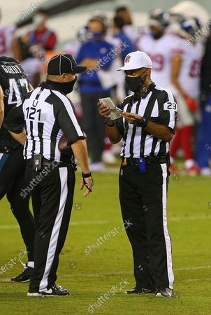 Umpire Paul King (121) tails with Referee Adrian Hill during an NFL football game between the New York Giants and Philadelphia Eagles, in Philadelphia