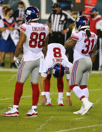 New York Giants' Daniel Jones (8) stretches after being sacked as Evan Engram (88) and Devonta Freeman (31) look on of an NFL football game against the Philadelphia Eagles, in Philadelphia. The Eagles defeated the Giants 22-21