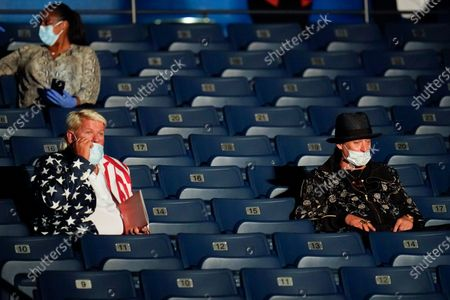 Pro golfer John Daly, left, and performer Kid Rock, right, take their seats before the start of the second and final presidential debate, at Belmont University in Nashville, Tenn