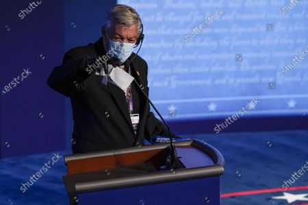 Technician cleans the microphone on President Donald Trump's podium before the second and final presidential debate, at Belmont University in Nashville, Tenn