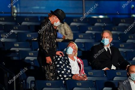 Performer Kid Rock, left standing, stops to talk with pro golfer John Daly, center, before the start of the second and final presidential debate, at Belmont University in Nashville, Tenn