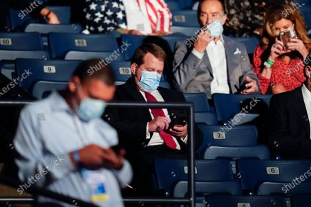 Tony Bobulinski, center seated, who says he is a former associate of Hunter Biden, uses his phone as he waits for the start of the second and final presidential debate, at Belmont University in Nashville, Tenn