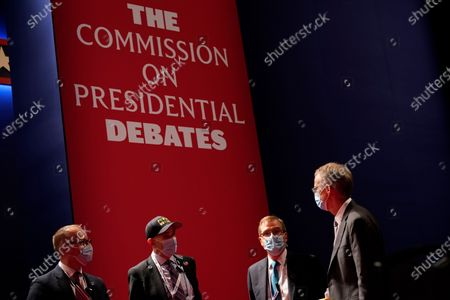 Officials from the Commission on Presidential Debates gather near the stage before the start of the second and final presidential debate, at Belmont University in Nashville, Tenn
