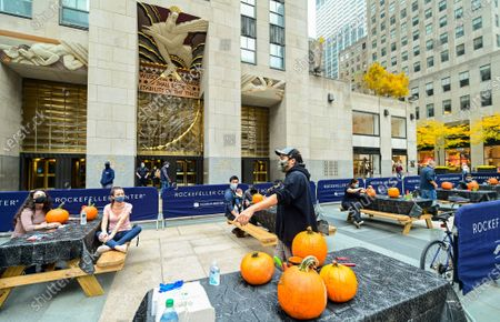 When pumpkin carving is a corporate amenity: Chris Soria, of Brooklyn's Maniac Pumpkin Carvers, teaches people working at Rockefeller Center how to carve jack o' lanterns for Halloween, . The class was part of Tishman Speyer's ZO. amenities program for all those who work in its buildings, and which includes in-person and virtual programming, transportation solutions, childcare and tutoring services