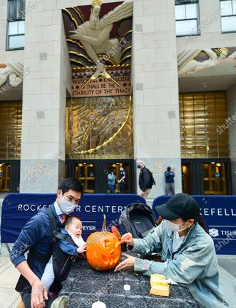 In preparation for Halloween, Anthony Pui and Miho Tabaru carve pumpkins with their daughter looking-on at Rockefeller Center on . People working at Rockefeller Center took a break to learn how to properly carve pumpkins from Maniac Pumpkin Carvers, artists from Brooklyn. The pumpkin carving class was part of Tishman Speyer's ZO. amenities program for all those who work in its buildings